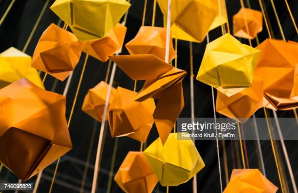 Low Angle View Of Orange And Yellow Origami Plane Decoration