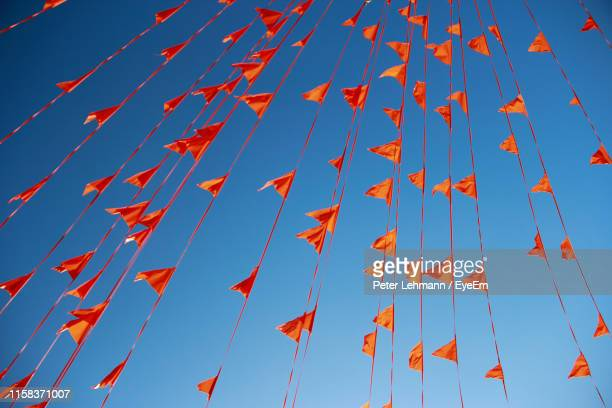 low angle view of orange buntings against clear blue sky - bunting stock pictures, royalty-free photos & images