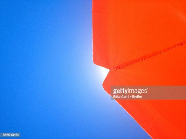 Low Angle View Of Orange Parasol Against Clear Blue Sky