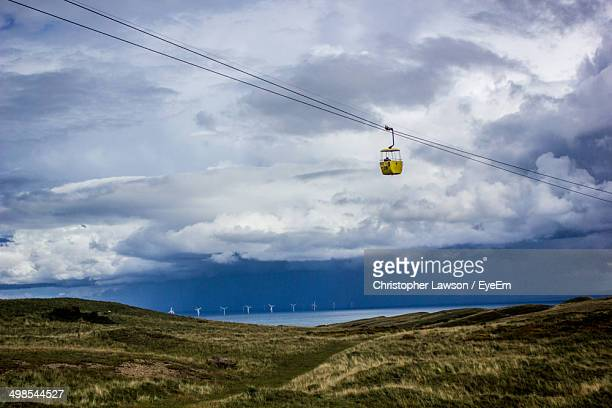 Low angle view of overhead cable car against clouds