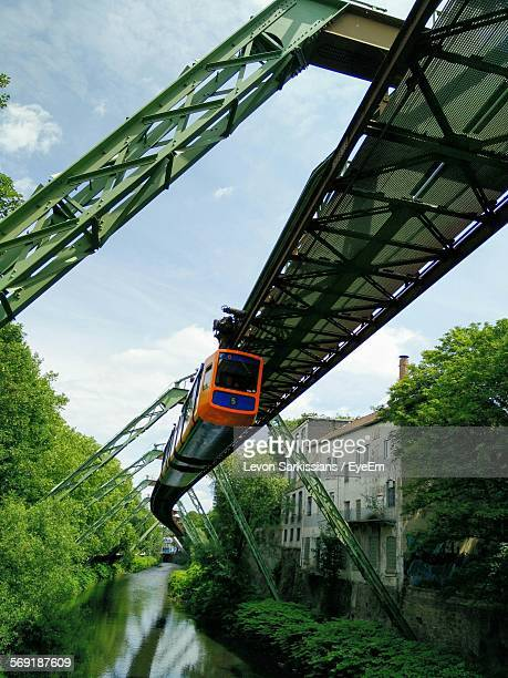 Low angle view of overhead cable car over river against sky