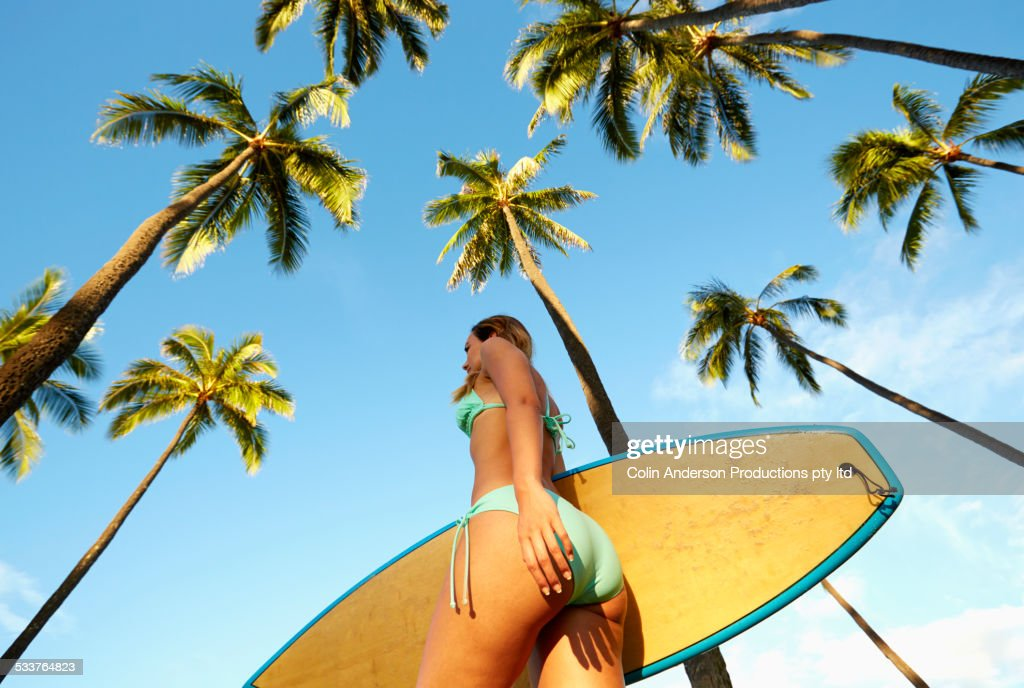 Low angle view of Pacific Islander woman carrying surfboard under palm trees : Foto stock