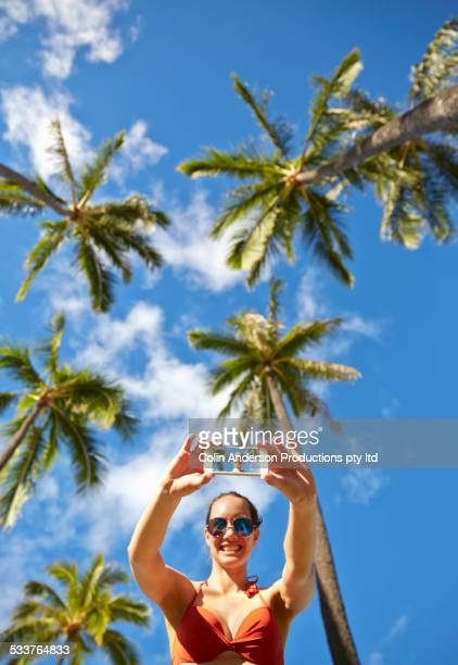 Low angle view of Pacific Islander woman taking cell phone selfie under palm trees
