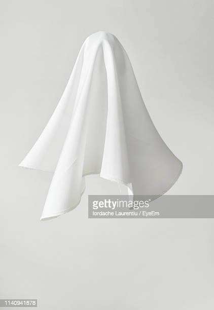 low angle view of paper in mid-air against white background - fantasma fotografías e imágenes de stock
