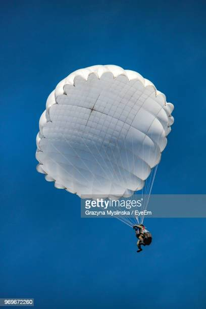 low angle view of parachute flying against clear blue sky - fallschirm stock-fotos und bilder