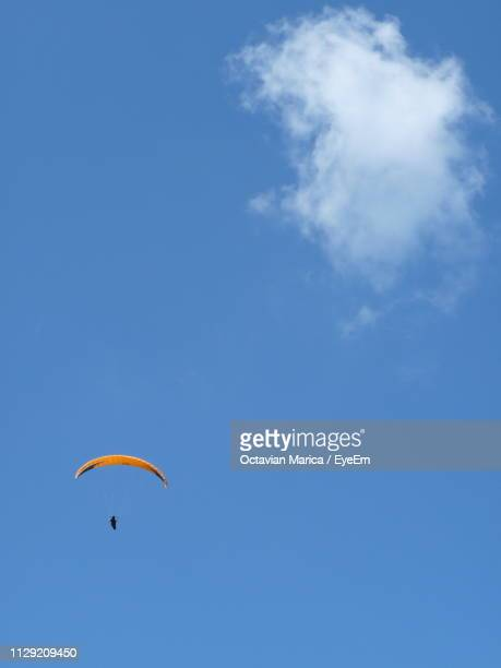 low angle view of parachute flying in blue sky - marica octavian stock photos and pictures