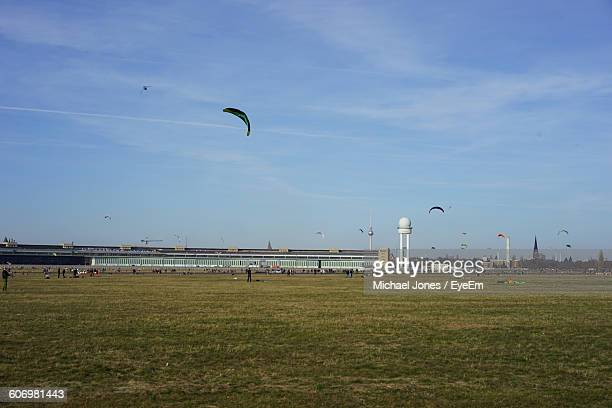 low angle view of parachutes flying over landscape against sky - tempelhof airport stock pictures, royalty-free photos & images
