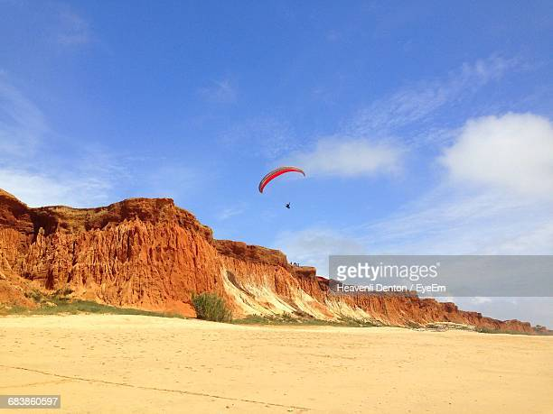 Low Angle View Of Paraglider Over Rock Formation At Praia Da Falesia Against Sky