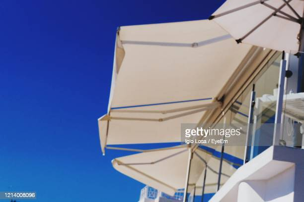 low angle view of parasol against clear blue sky - puerto del carmen stock pictures, royalty-free photos & images