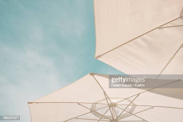 low angle view of parasol against sky - sunshade stock pictures, royalty-free photos & images