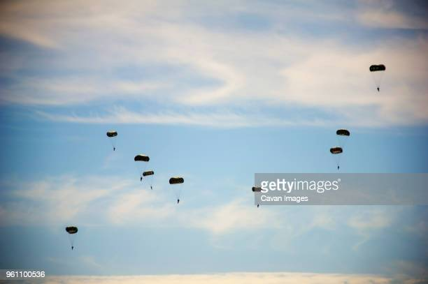 low angle view of paratroopers flying in sky during airshow - paratrooper stock pictures, royalty-free photos & images
