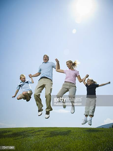 Low angle view of parents and their two children jumping