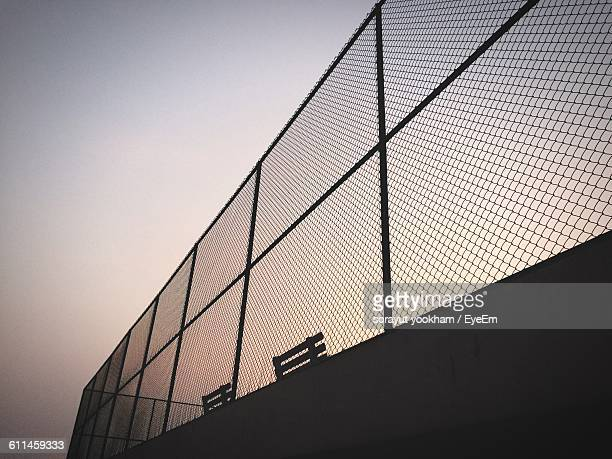 Low Angle View Of Park Benches By Chainlink Fence Against Clear Sky During Sunset