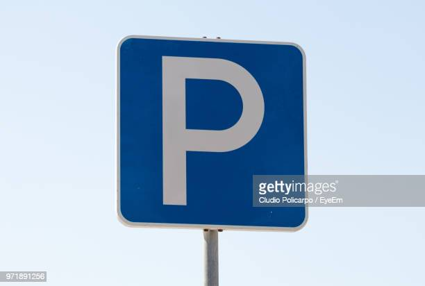 low angle view of parking sign against clear sky - parking sign stock photos and pictures