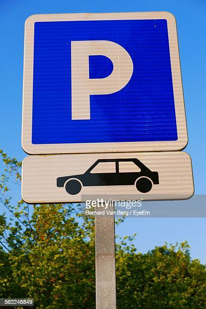 Low Angle View Of Parking Sign By Tree Against Clear Blue Sky