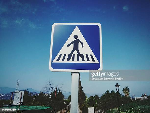 low angle view of pedestrian crossing sign against blue sky - pedestrian crossing sign stock photos and pictures