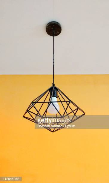 low angle view of pendant light hanging on ceiling - pendant light stock pictures, royalty-free photos & images