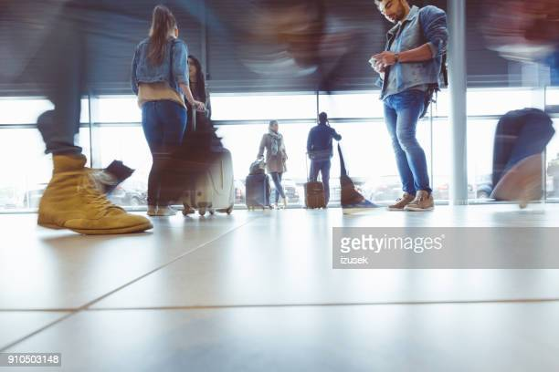 Low angle view of people at airport terminal, blurred motion