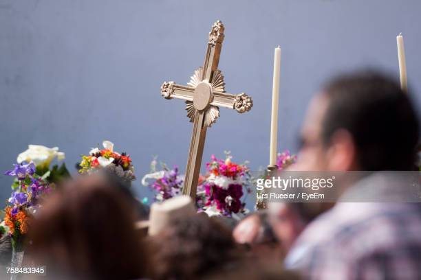 Low Angle View Of People Carrying Cross On Street During Easter Procession