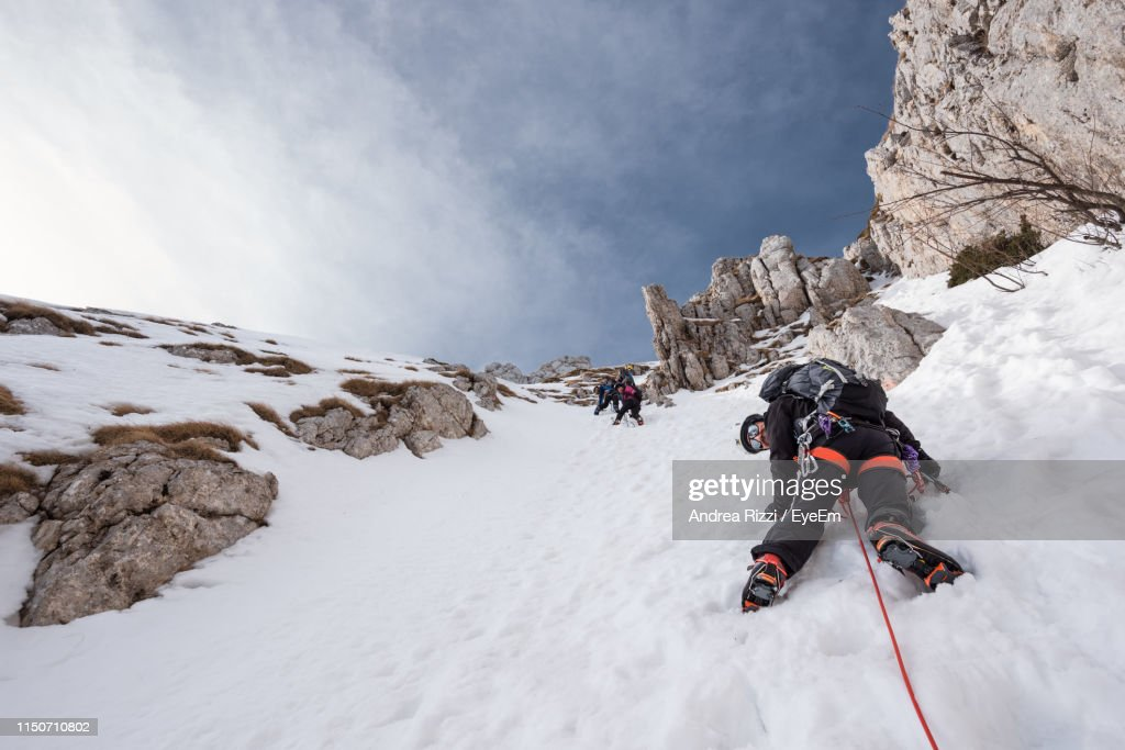 Low Angle View Of People Climbing Snow Covered Mountain Against Sky : Foto stock