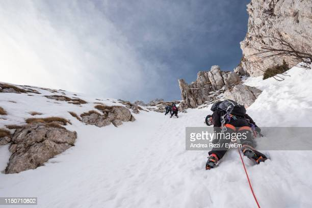 low angle view of people climbing snow covered mountain against sky - andrea rizzi stockfoto's en -beelden