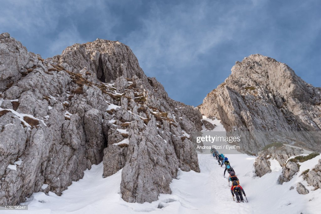 Low Angle View Of People Climbing Snow Covered Mountain : Stock Photo
