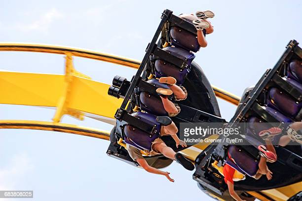 Low Angle View Of People Enjoying Roller Coaster Ride