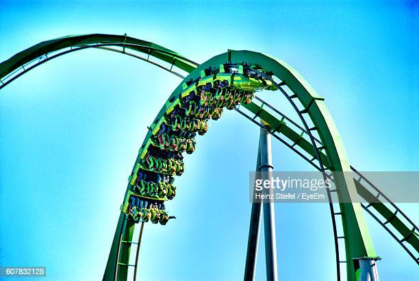 Low Angle View Of People Enjoying Rollercoaster Against Blue Sky