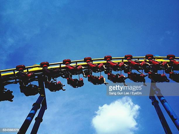 Low Angle View Of People Enjoying Rollercoaster Ride Against Sky