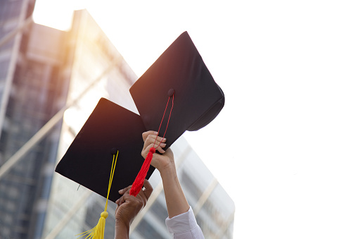 Low Angle View Of People Hands Holding Mortarboards Against Sky - gettyimageskorea
