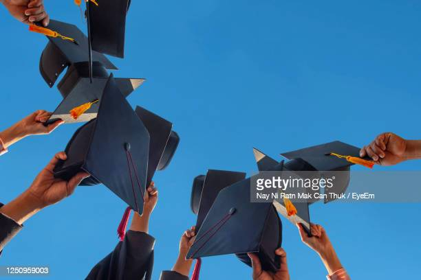 low angle view of people holding cap against clear sky - ceremony stock pictures, royalty-free photos & images