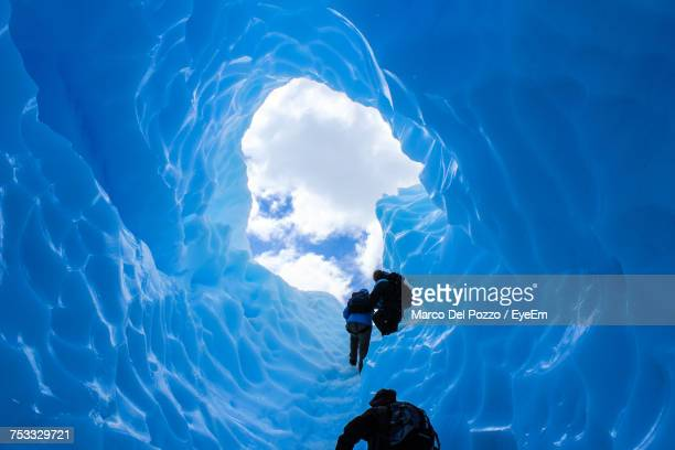 Low Angle View Of People In Ice Cave