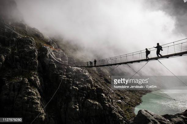 low angle view of people on footbridge against mountains - suspension bridge stock pictures, royalty-free photos & images