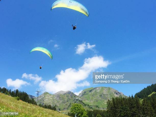 Low Angle View Of People Paragliding Against Blue Sky During Sunny Day