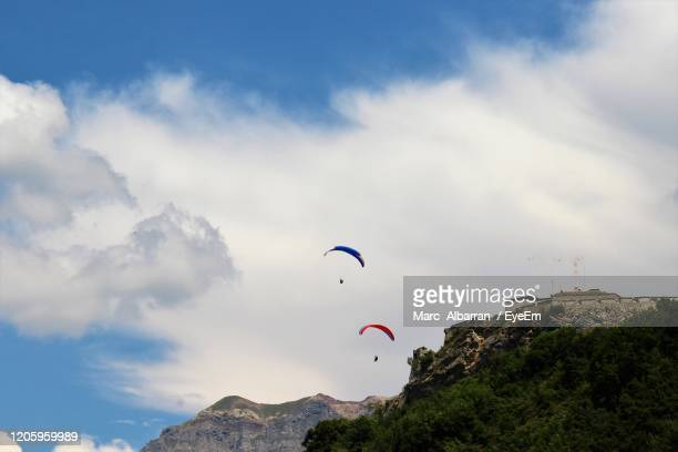 low angle view of people paragliding against sky - embrun stock pictures, royalty-free photos & images