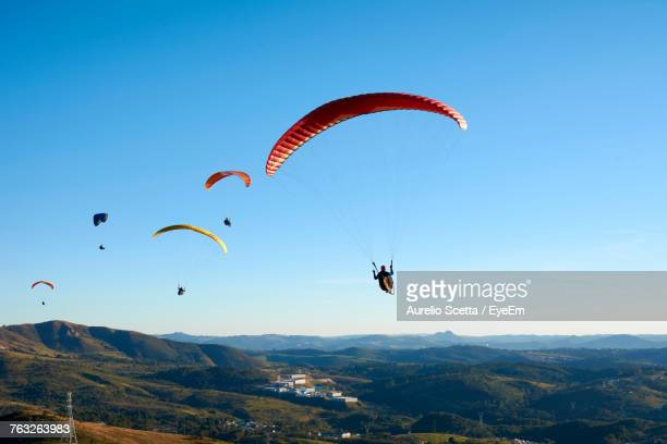 low angle view of people paragliding over mountains against clear sky - gliding stock photos and pictures