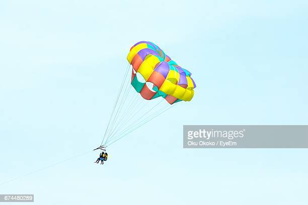 Low Angle View Of People Parasailing Against Clear Sky