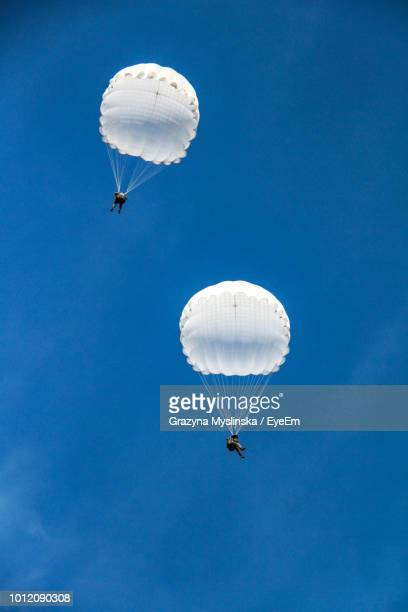 Low Angle View Of People Parasailing In Blue Sky