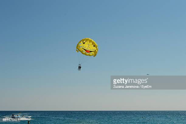 Low Angle View Of People Parasailing Over Sea Against Sky