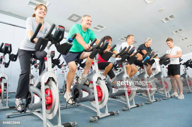 Low angle view of people riding spin bicycles in gym