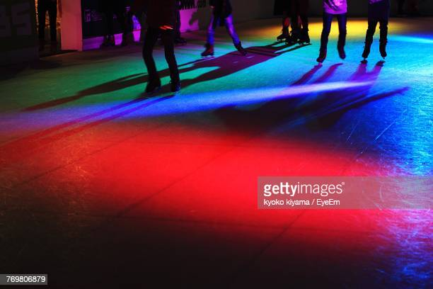 Low Angle View Of People Skating On Multi Colored Ice Rink