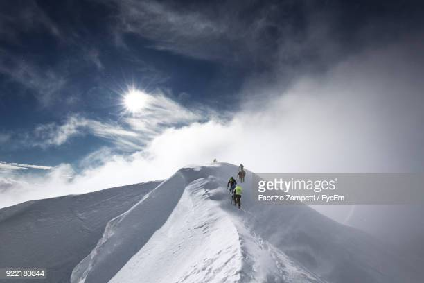 low angle view of people skiing on snow covered mountain - vetta foto e immagini stock