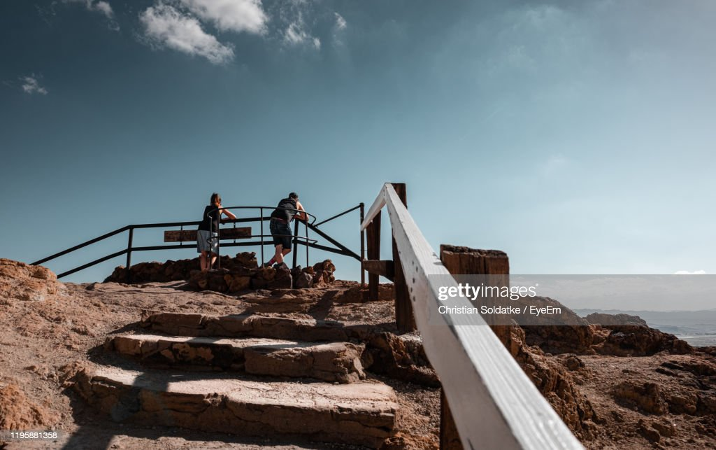 Low Angle View Of People Standing By Railing Against Sky : Stock-Foto