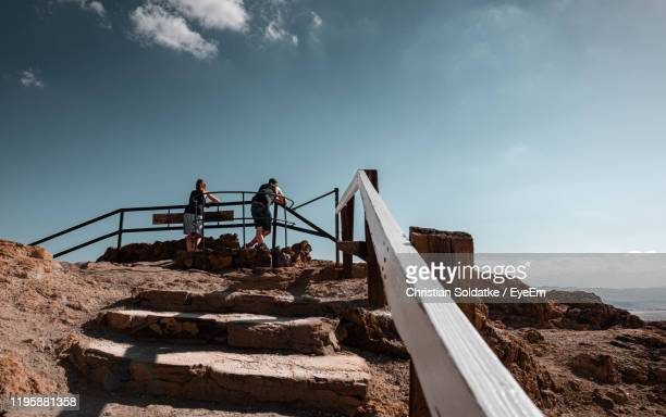 low angle view of people standing by railing against sky - christian soldatke fotografías e imágenes de stock