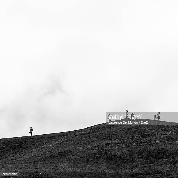 Low Angle View Of People Standing On Hill