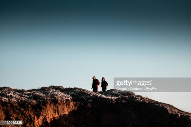 low angle view of people standing on mountain against sky - christian soldatke stock-fotos und bilder