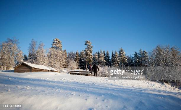 Low Angle View Of People Standing On Snow Covered Hill By Trees During Winter