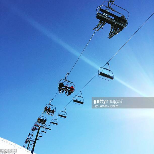 Low Angle View Of People Traveling In Overhead Cable Cars Against Blue Sky