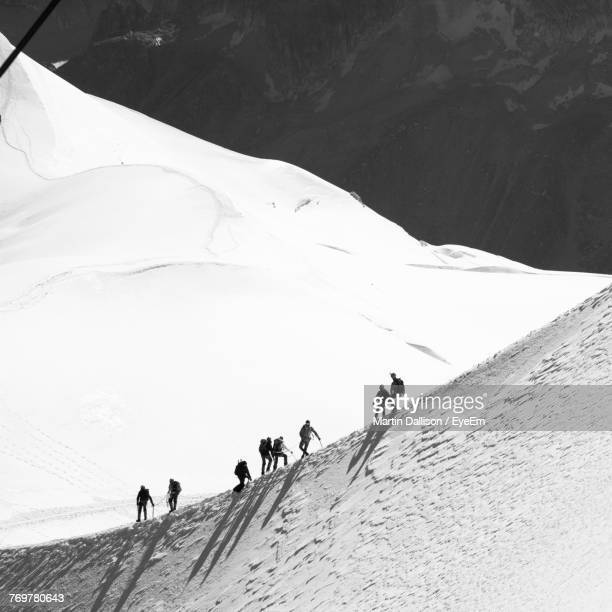 Low Angle View Of People Walking On Snowcapped Mountain During Sunny Day