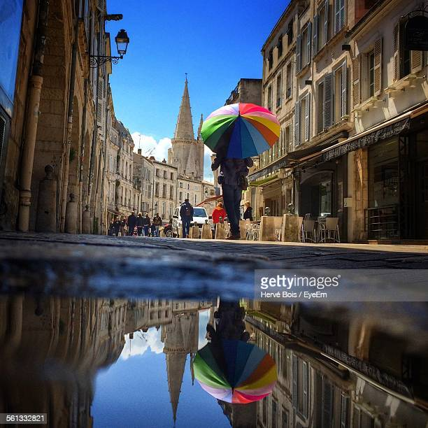 low angle view of people walking on street amidst buildings in city - la rochelle stock pictures, royalty-free photos & images